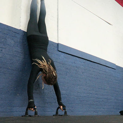 Wall handstand on push up bars