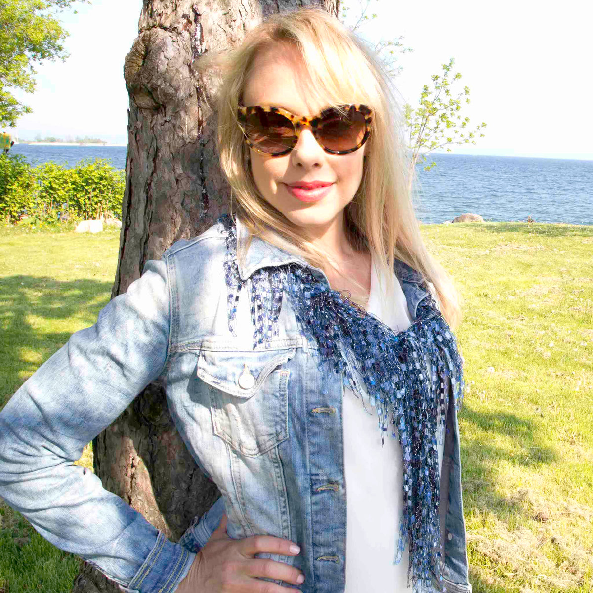 women leaning against tree in park wearing denim jacket, sunglasses and blue scarf necklace
