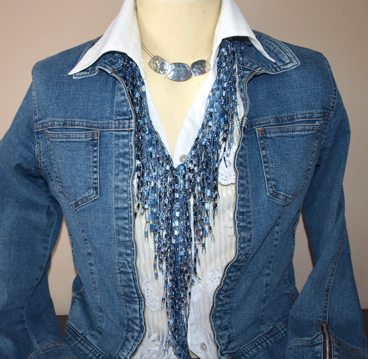 mannequin showing blue jean jacket and blue scarf necklace