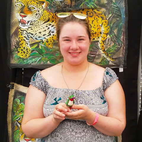 Customer with fair-trade woven bird ornament at CACE booth at Falcon Ridge Folk Festival 2019