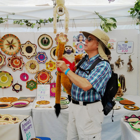 Man with monkey puppet at CACE booth at Falcon Ridge Folk Festival 2019