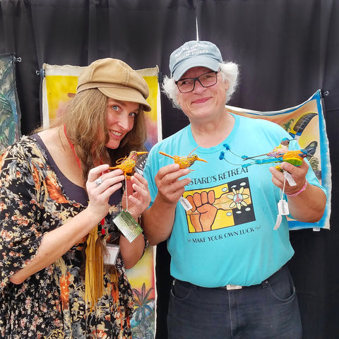 Customers with fair-trade woven bird ornaments at CACE booth at Falcon Ridge Folk Festival 2019