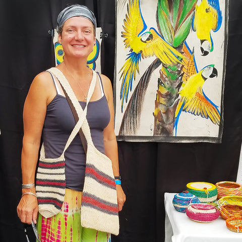 Customer with fair-trade hand made bottle carrier and shoulder bag at CACE booth at Falcon Ridge Folk Festival 2019