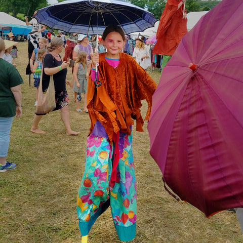 Girl on stilts in front of CACE booth at Falcon Ridge Folk Festival 2019