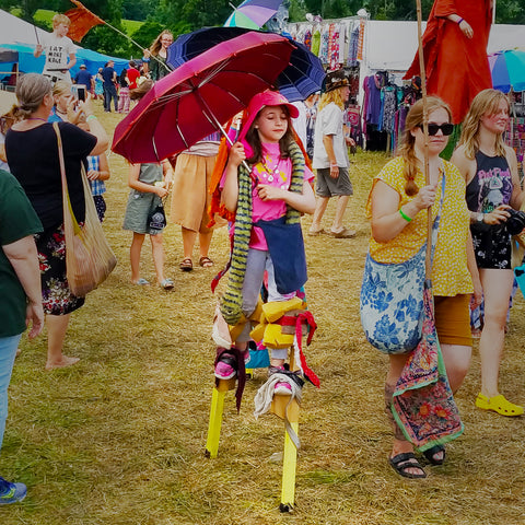 Girl on stilts in parade in front of CACE booth at Falcon Ridge Folk Festival 2019