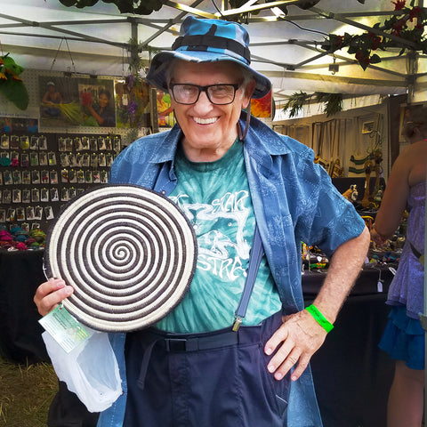 Customer with fair-trade placemat at CACE booth at Falcon Ridge Folk Festival 2019