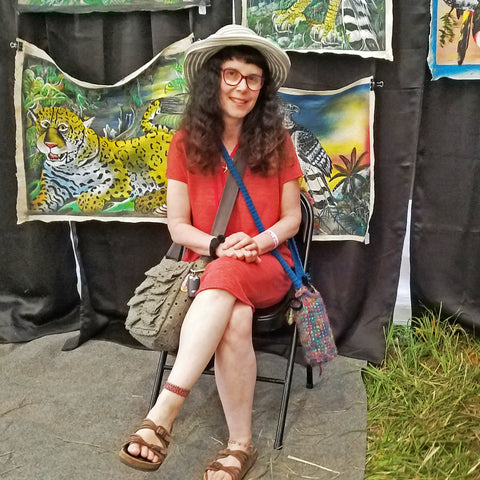 Customer with Amazon seed anklet at CACE booth at Falcon Ridge Folk Festival 2019