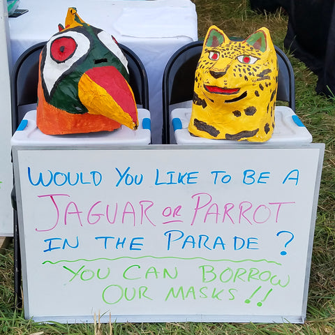 Parrot and jaguar head masks at CACE booth at Falcon Ridge Folk Festival 2019