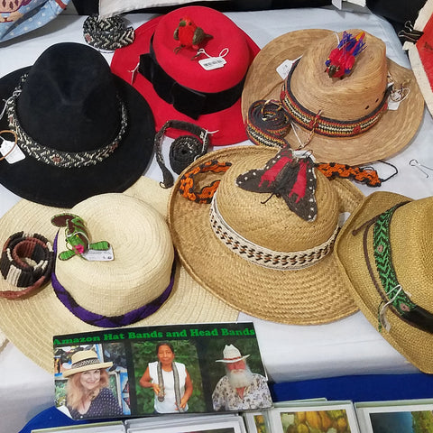 Wildlife ornaments woven with chambira palm fiber on hats at the CACE booth at the Philadelphia Folk Festival 2019