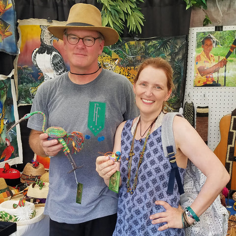 Couple with Amazon bird ornaments woven with chambira palm fiber at the CACE booth at the Philadelphia Folk Festival 2019
