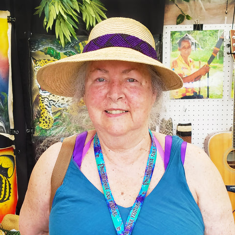 Woman with hand-made hat band woven with chambira palm fiber at the CACE booth at the Philadelphia Folk Festival 2019
