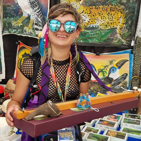 Woman with fair-trade guitar strap and hand-made ornaments at the CACE booth at the Philadelphia Folk Festival 2019