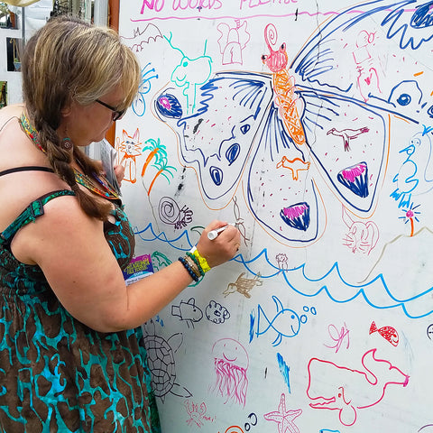 Woman drawing on the Community Nature Art mural at the CACE booth at the Philadelphia Folk Festival 2019