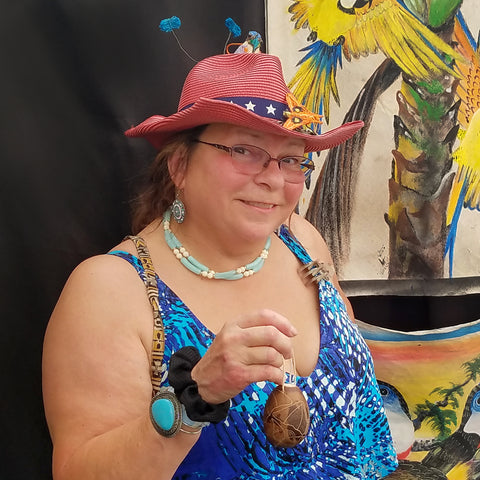 Woman with calabash rattle and hummingbird ornament on hat at CACE booth at Rhythm and Roots Festival 2019