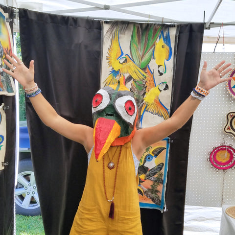 Woman in toucan maks at CACE booth at Rhythm and Roots Festival 2019