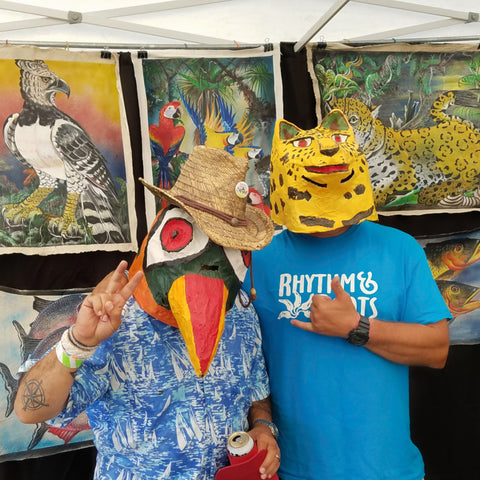 Visitors in jaguar and toucan masks at CACE booth at Rhythm and Roots Festival 2019.