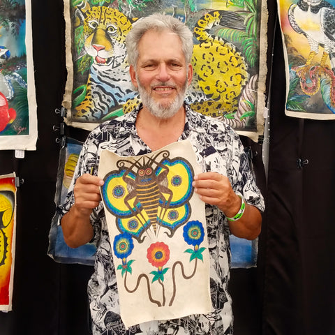 Man with llanchama tree bark painting at CACE booth at Rhythm and Roots Festival 2019