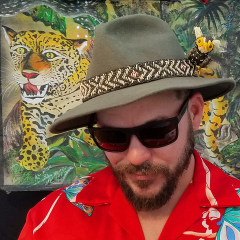 Man with bird ornament fascinator and hatband at CACE booth at Romp Festival 2019
