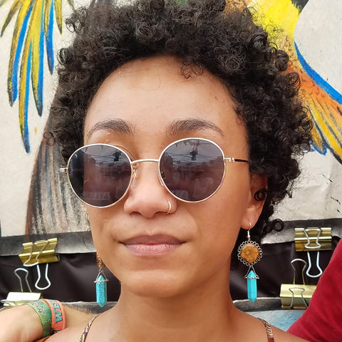 Woman with ayahuasca vine and turquoise earrings at CACE booth at Romp Festival 2019