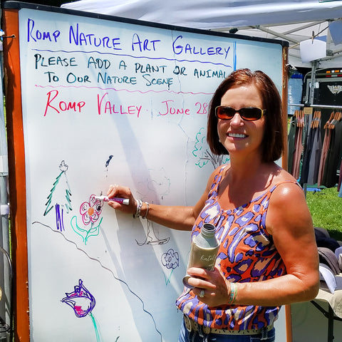woman drawing on community art board at CACE booth at Romp Festival 2019