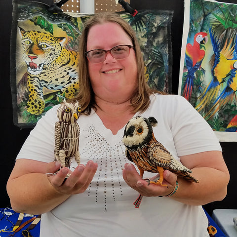 Woman customer with owl ornaments at CACE booth at Romp Festival 2019