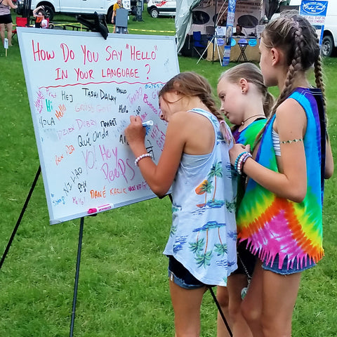 three girls at How do say hello in your language board at CACE booth at Romp Festival 2019