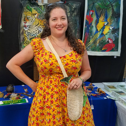 customer with chambira bottle carrier and butterfly ornament at CACE booth at Romp Festival 2019