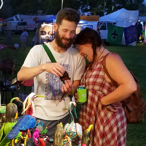 Couple checking out a bird ornament at CACE booth at Romp Festival 2019