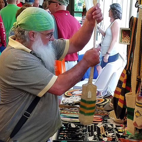 Man shops for woven bottle carrier at the CACE booth at the Strawberry Festival 2019