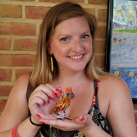 Woman with woven hoatzin bird ornament at the CACE booth at the Strawberry Festival 2019