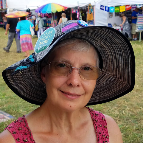 Customer with hand-made butterfly barrette on hat at CACE booth at Falcon Ridge Folk Festival 2019