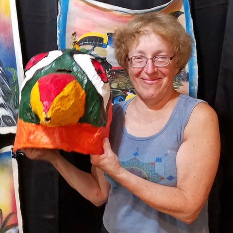 Customer with parrot-head mask at CACE booth at Falcon Ridge Folk Festival 2019