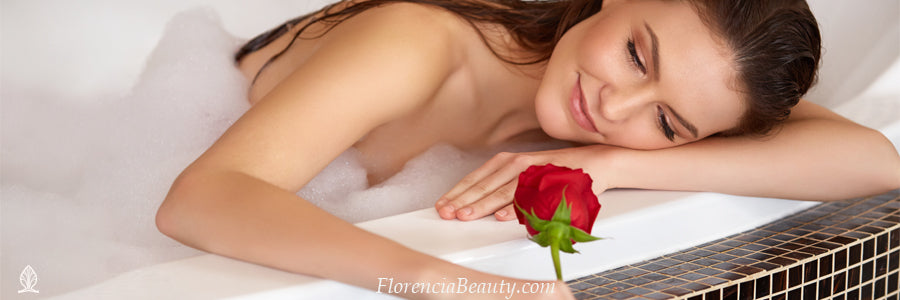 woman resting her head on the bathtub with a red rose