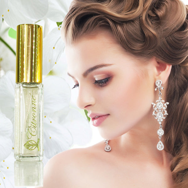 A small spray bottle of Citronné Fragrance in a clear bottle with gold top. Profile of a woman looking down with her hair half up and long shiny earrings.