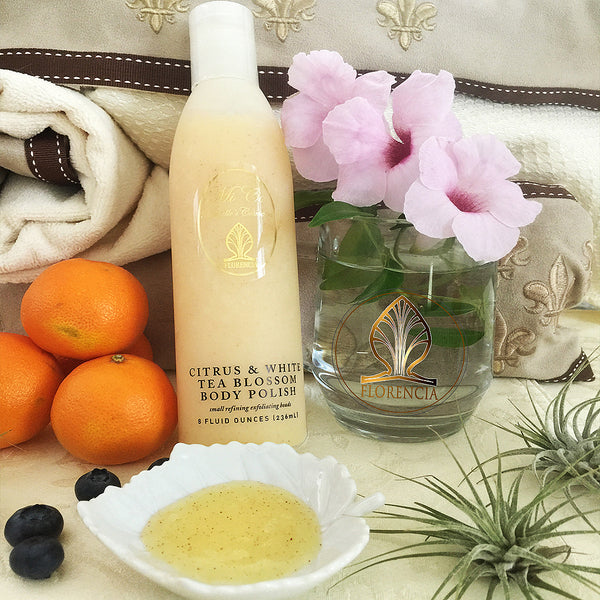 A bottle of Citrus & White Tea Blossom Body Polish resting against fabrics with oranges, blueberries and flowers next to it. Small leaf dish with the polish.