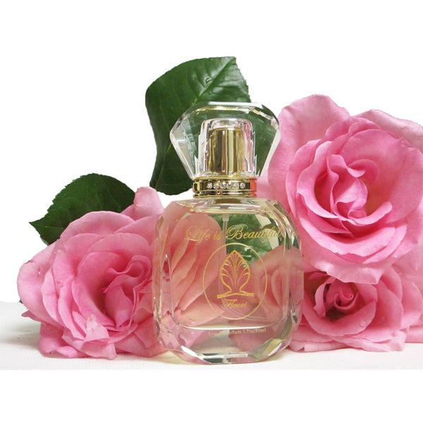 Fleuri Perfume bottle in front of pink roses.