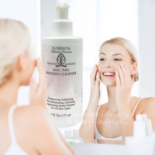 Woman with her hands on her cheeks looking into the mirror, washing her face with a bottle of AHA / BHA Refining Cleanser