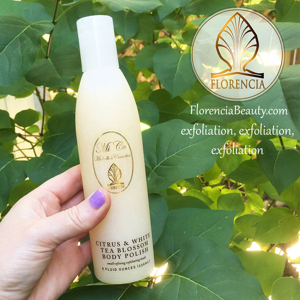 A hand holding a bottle of Citrus & White Tea Blossom Body Polish with greenery in the background.