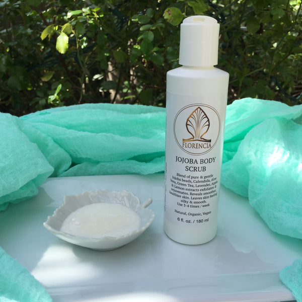 A Jojoba Body Scrub bottle with a white leaf dish on an outdoor table.