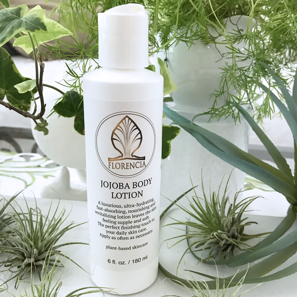 Open bottle of Jojoba Body Lotion by Florencia on the table with green plants