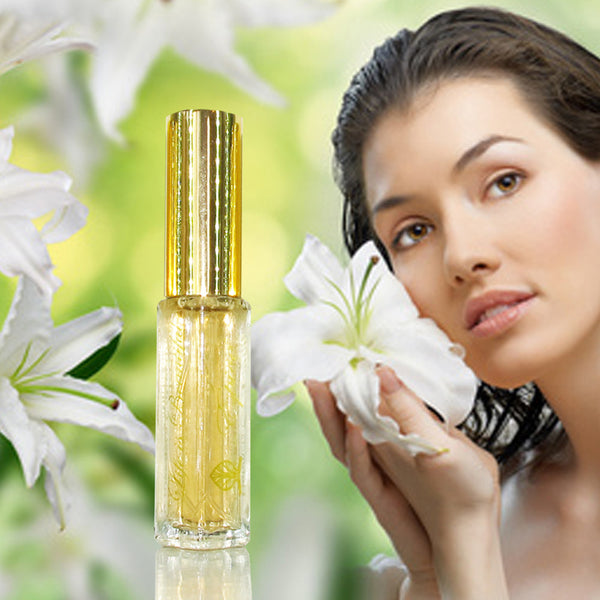 A bottle of Épicé Fragrance spray with a clear bottle and gold lid. Woman holding a flower against her cheek.