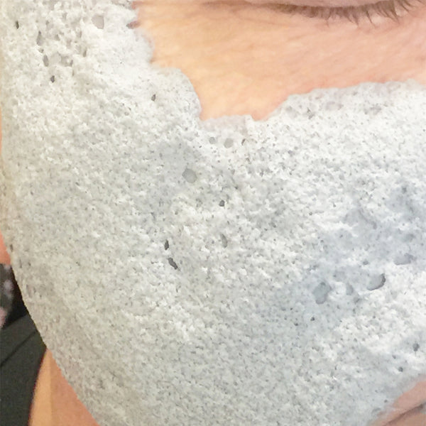 Close up of the White Charcoal O2 Detox Masque on a womans face.