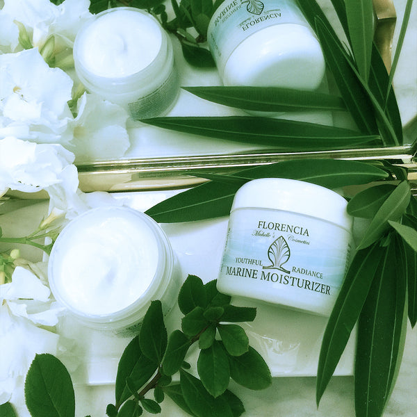 Jars of Marine Moisturizer Youthful Radiance reflecting in the mirror with greenery.