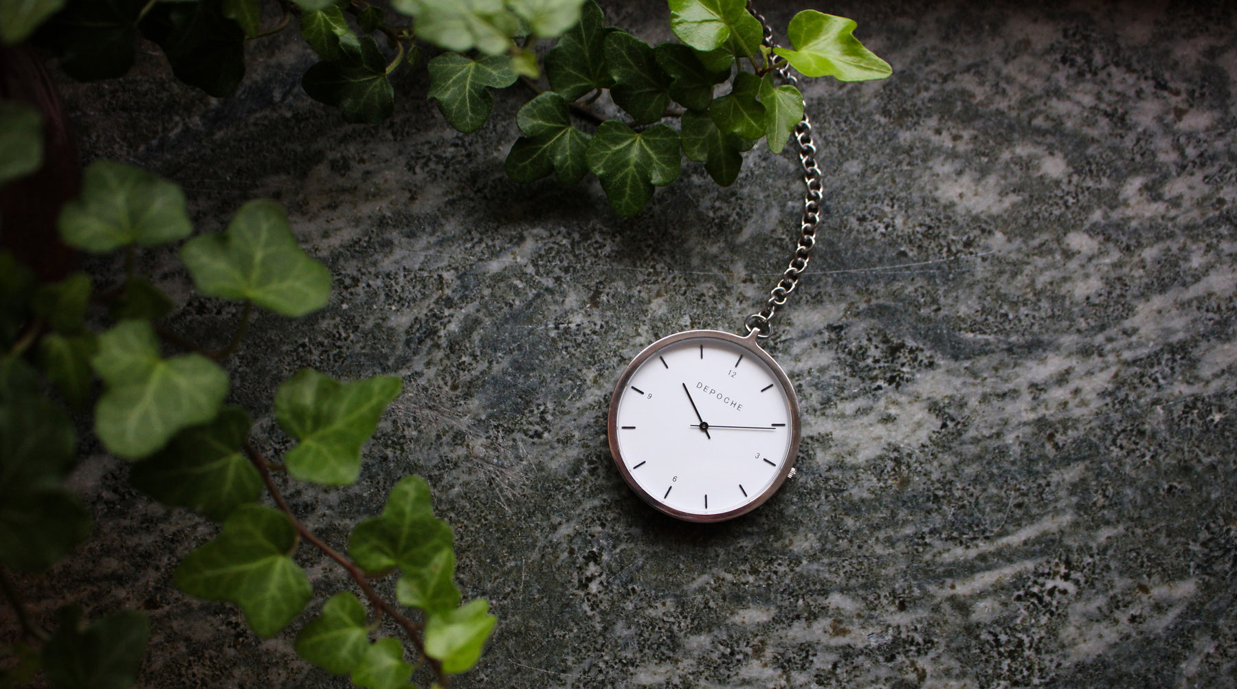 Depoche silver pocket watch on marble