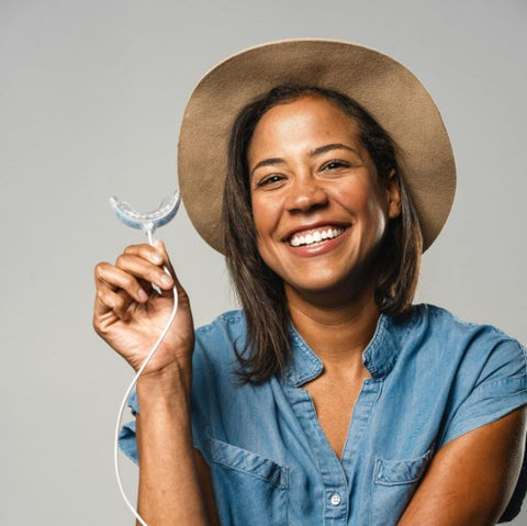 women with hat smiling while holding a snow teeth whitening tray