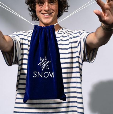 joyful young man holding drawstring bag with snow logo