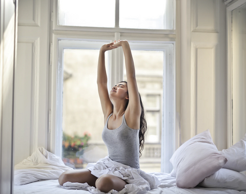 young girl stretching her body after waking up from sleep