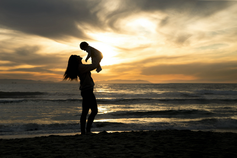 mom playing with her child in sea beach
