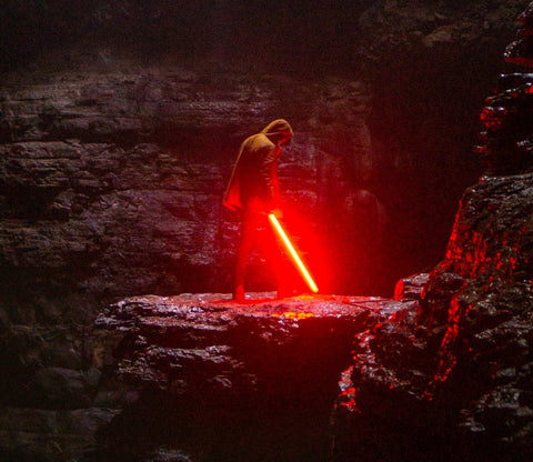 man standing in a cliff with a lightsaber in hand