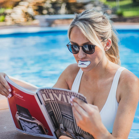 Women in white bathing suit reading a magazine next to the pool